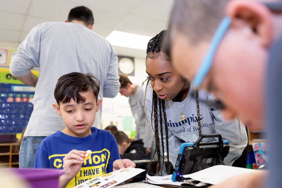 Junior Achievement volunteer Coralie Joseph '19, management, introduces kindergarteners to the world of business and entrepreneurship at Cook Hill Elementary School in Wallingford, CT for the annual Quinnipiac School of Business Community Service Day Friday, April 5, 2019.