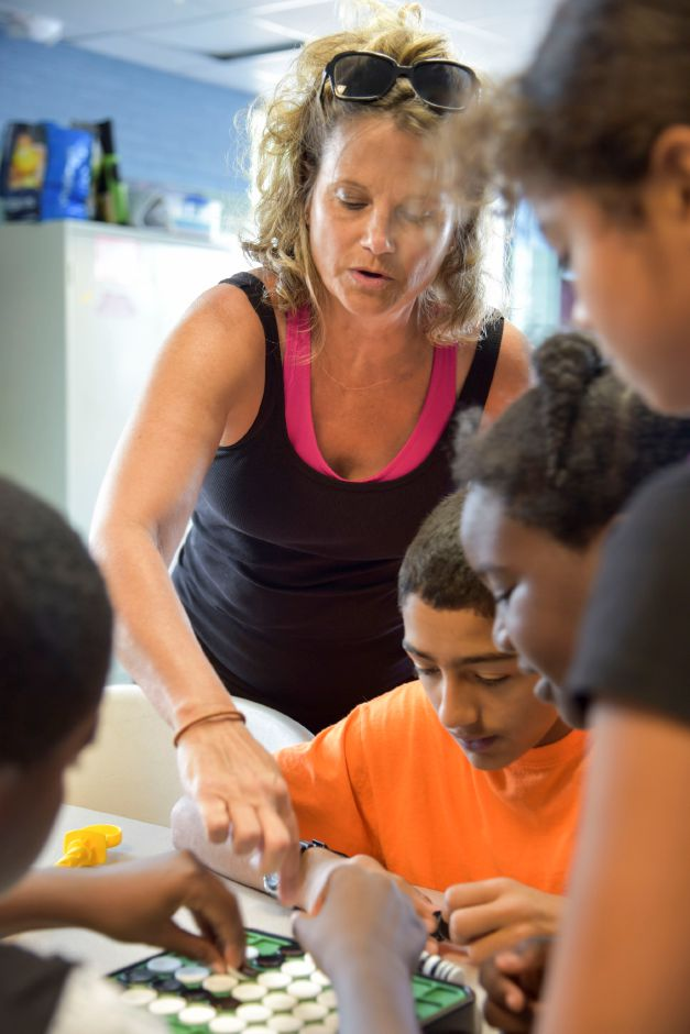 Boys & Girls Club mentor Debbie Clark, of Meriden, helps students play Othello at the club on Wednesday, Sept. 19. The club is looking to expand its mentorship program. | Bailey Wright, Record-Journal