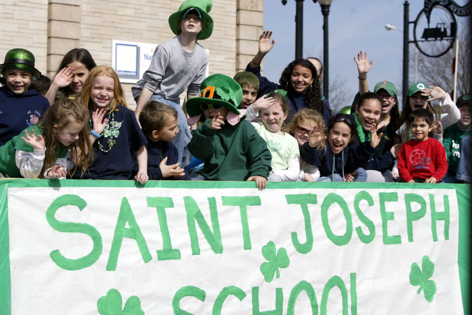 Students from St. Joseph School waive to the crowd from their float in the St. Patrick