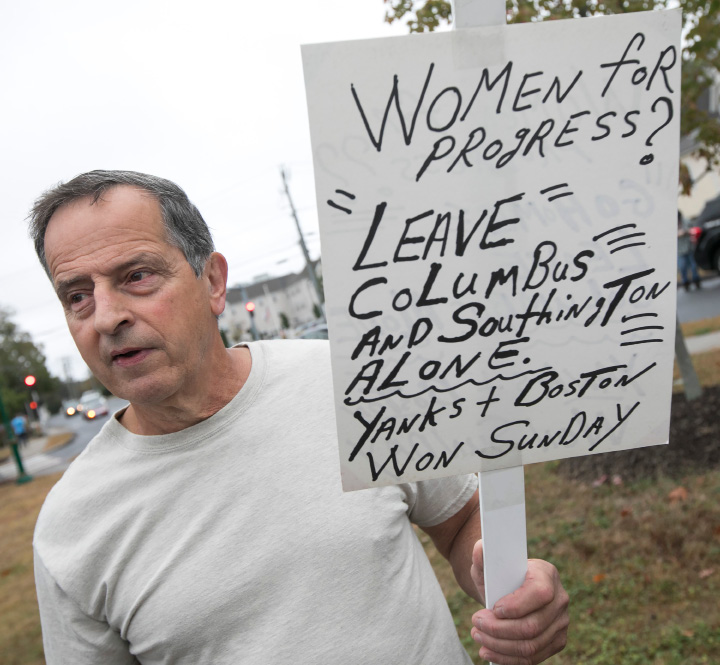 Counter-protester, Rick Casale, of Southington, holds a sign during a dedicaton and unveiling of a Christopher Columbus monument at Southington