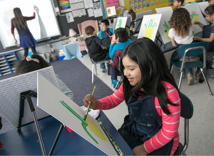 "Yahara Sanchez, 7, paints her own version of Vincent van Gogh's ""Sunflowers"" during a workshop for the second-graders led by city artist Karen Jaime at John Barry School in Meriden on Tuesday.