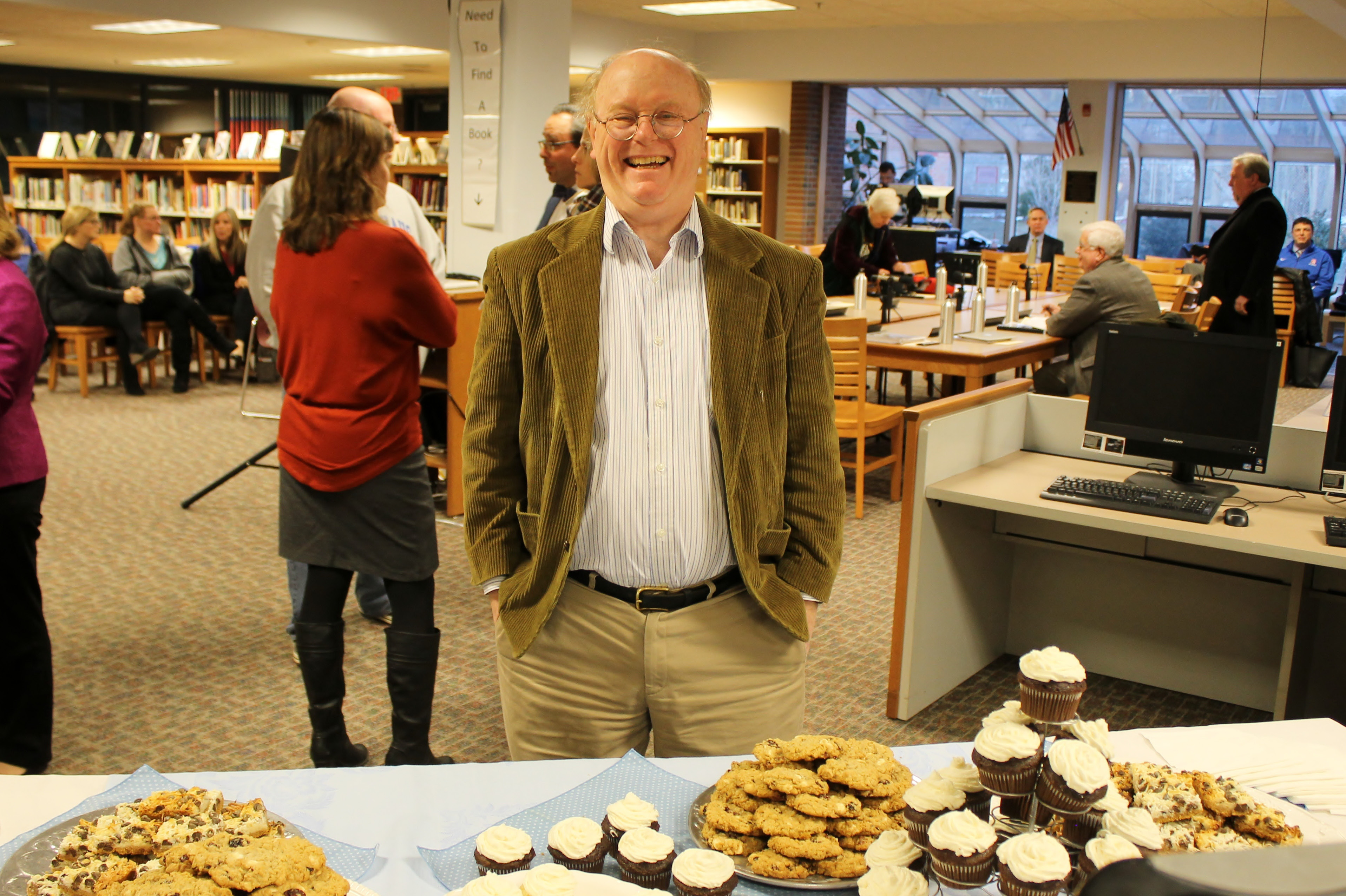 Board of Education member Victor Friedrich pauses before a table of baked goods at the BOE