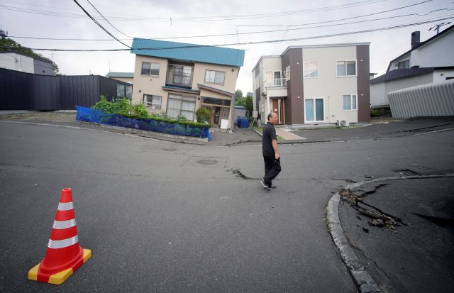 A resident walks by damaged houses in Kiyota, outskirts of Sapporo city, Hokkaido, northern Japan, Friday, Sept. 7, 2018. A powerful earthquake hit wide areas on Japan