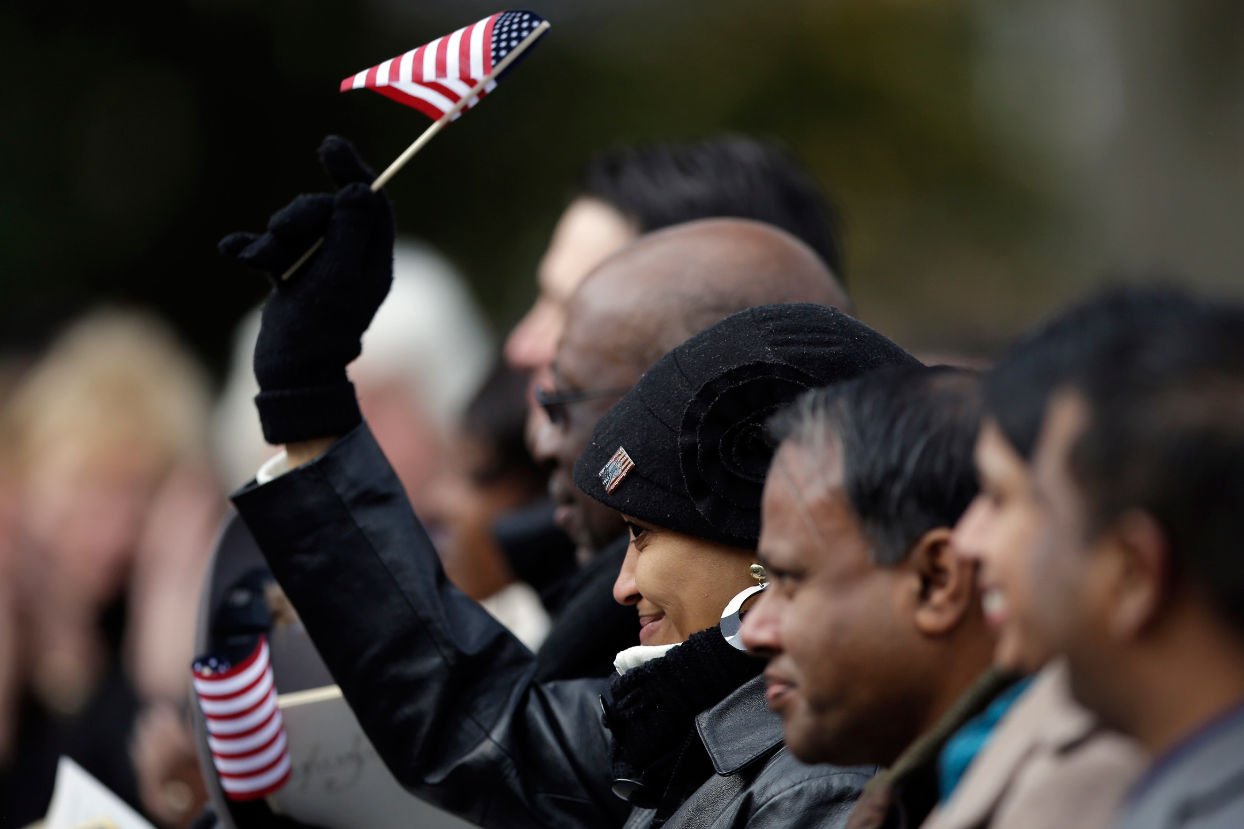 A new citizen waves a flag after Supreme Court Justice Antonin Scalia administered the oath of allegiance, during a ceremony commemorating the 150th anniversary of the dedication of the Soldiers National Cemetery and President Abraham Lincoln