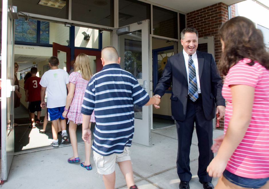 Dr. Salvatore Menzo, superintendent of schools, greets students at Yalesville Elementary school Tuesday morning on the first day of school in Wallingford, August 31, 2010. When he was greeting students, Menzo was carefully watching his email on his smartphone in case there were any bus problems on the first morning of the new school year with the elementary school reconfiguration. (Christopher Zajac/Record-Journal)