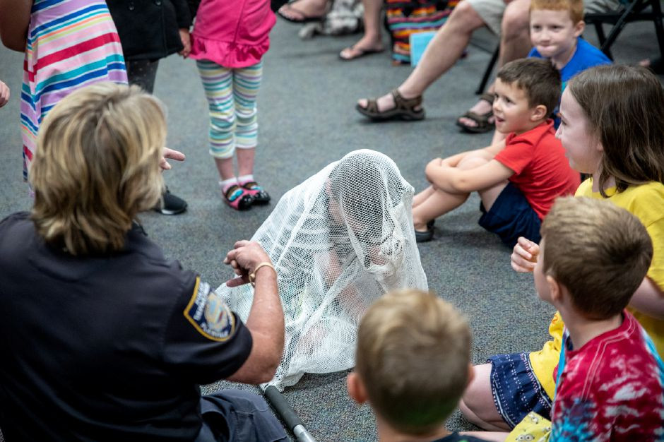 Plainville Animal Control Officer Donna Weinhofer traps a child in a net at the Plainville Public Library. Weinhofer visited the library Tuesday night to help families understand the animals which live around them. | Devin Leith-Yessian / Plainville Citizen