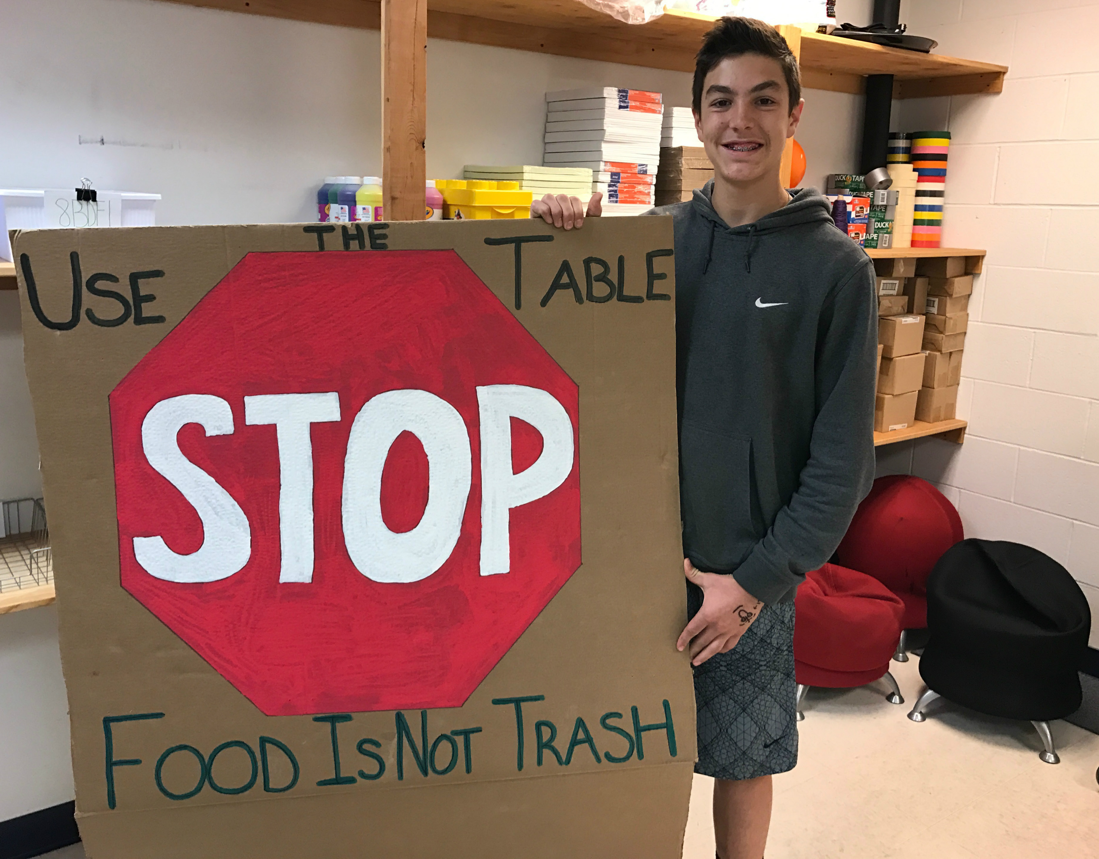 Moran Middle School 8th grader  Nick Iannone holds a sign encouraging students to not waste unused food. | Matthew Zabierek, Record Journal