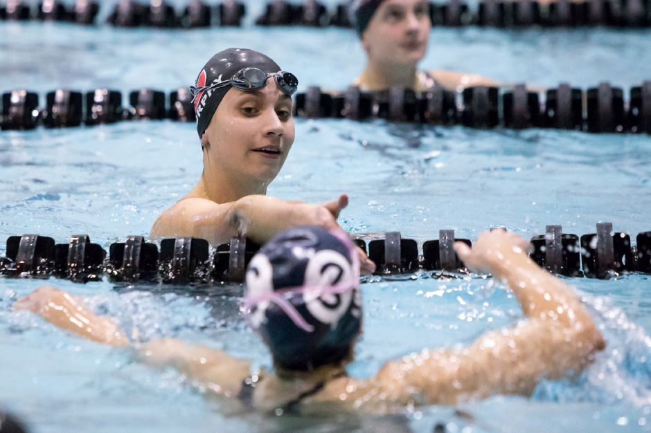 Cheshire's Sophie Murphy reaches to shake hands with Wilton's Taylor Loud. Murphy won her two individual races, the 50-yard freestyle and the 100-yard freestyle.