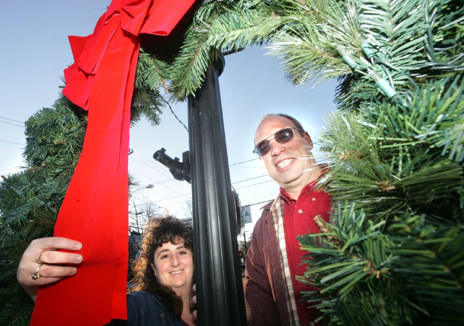 Aprill Ouellette, left, and Ed Haberli pose together looking through a wreath they had hung on a lamp post in South Meriden recently. The two are part of the crew that works hard to set up the Christmas in the Village event in South Meriden each year. Chris Angileri/Record-Journal.