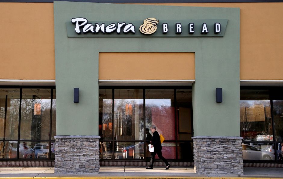 In this Wednesday, April 12, 2017, photo, a passer-by walks near an entrance to a Panera Bread restaurant location, in Natick, Mass. (AP Photo/Steven Senne)