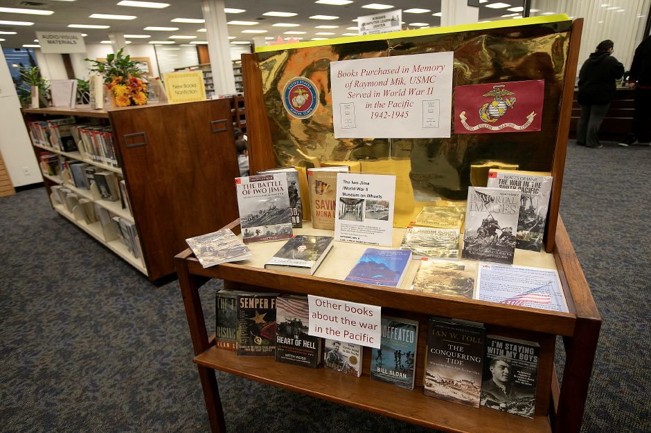 At left, books about the war in the Pacific on display at the Meriden Public Library. The books were purchased in memory of Raymond Mik, USMC who served in WWII in the Pacific from 1942-1945.