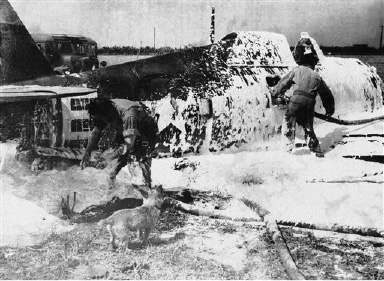 "Here's what happens when a Thunderbolt P-47 crash lands and bursts into flames, August 31, 1943, necessitating prompt action upon the part of the station crash crew. This Thunderbolt hit a wind sock on the field during a take off, and the pilot managed to belly land the plane, albeit the motor was left some 40 yards behind the fuselage. The foamy substance is used to put out the fire which broke out immediately upon the plane's striking the ground. However the pilot, 2nd Lt. Robert F. Brow of 635 W. Boone, Str. Piqua, Ohio, walked away with merely singed eyebrows. The crash crew consisted Pfc. Emile J. Nussbaum, New Orleans, La.; Pte. Harlem Nickerson, Spruce St., So. Pasadena, Cal. And Pte. Van Keuren, Liberty, N.Y. One of the station's mascots, a tiny terrier named ""Thruppence"" we the proceedings as Nussbaum and Van Keuren fight fire. (AP Photo)"