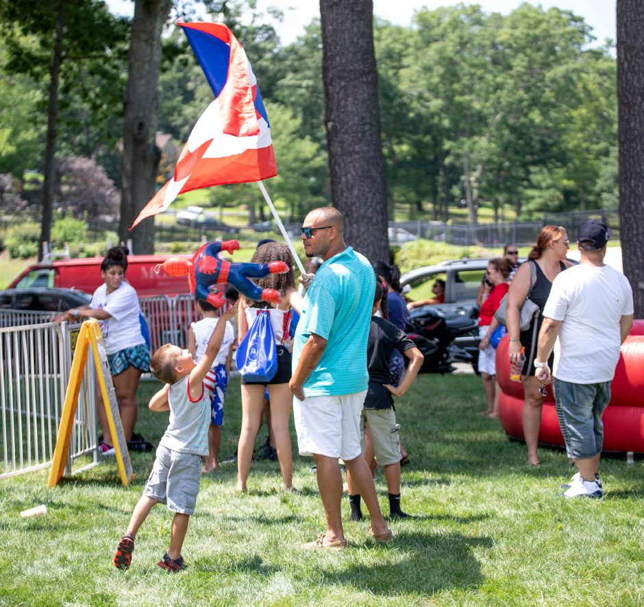 Devin Cordero, 4, throws his Spiderman toy at a Puerto Rican flag held by Edin Cordero, of Meriden, at the Meriden Puerto Rican Festival on August 5, 2018. | Devin Leith-Yessian/Record-Journal