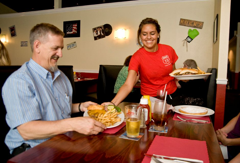 Waitress Hillary Brown serves a hamburger and fries to Steve Pintarich at the Route 10 Tavern in Southington, July 6, 2011. The Route 10 Tavern opened for business on June 24th and sports an Americana motif. (Sarah Nathan/Record-Journal)