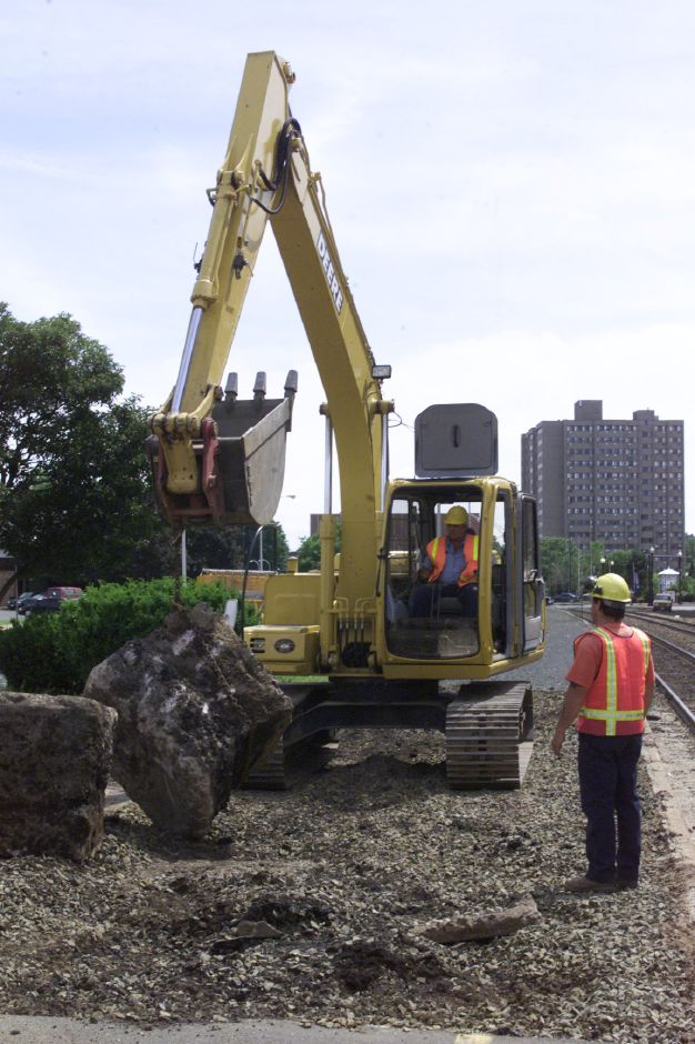 The Meriden Water Division cleans up as part of the Canopy Project for the train station. Peter Standish of Meriden watches as Gary Graham, also of Meriden maneuvers the back-hoe to lift the old canopy foundations.