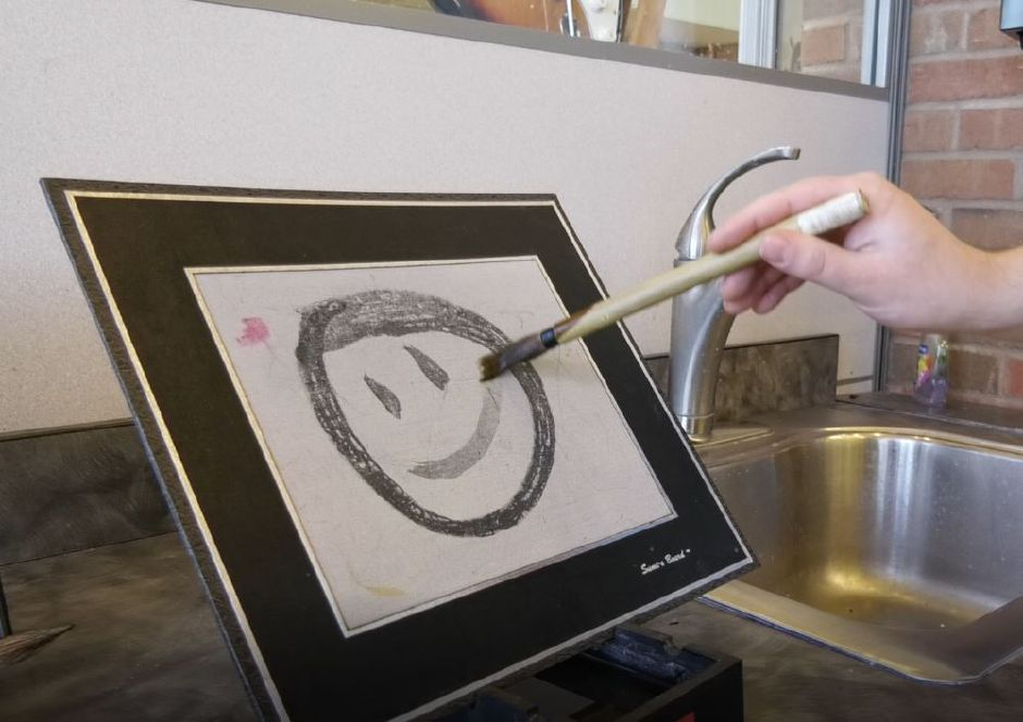 Max Spurr, Creative Technologies Librarian, draws a smiley face on a water-based art pad in the Collaboratory makerspace at Wallingford Public Library, 200 North Main St., Wallingford. | Ashley Kus, Record-Journal