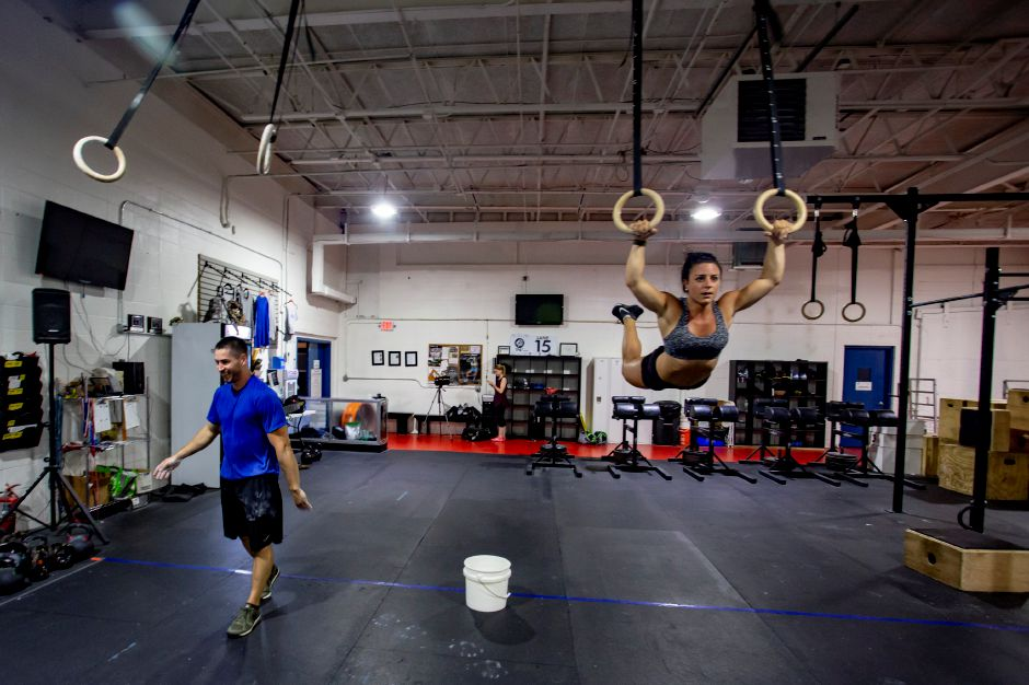 Coach Brandon Threloff laughs after doing a set on the rings with fellow coach Giani Ives at the Meriden Crossfit Aug. 29, 2018. | Richie Rathsack, Record-Journal