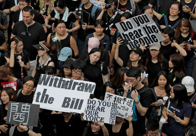 FILE - In this Sunday, June 16, 2019, file photo, protesters holding posters and flowers march on the streets to protest against the unpopular extradition bill in Hong Kong. (AP Photo/Vincent Yu, File)