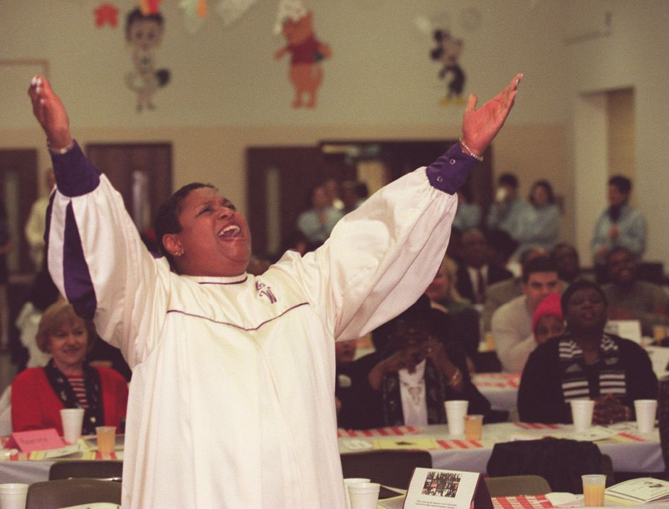 RJ file photo - G. Ingrid Faniel, director of the Alfred E. White Chorale of Hartford, lifts her arms up to the Lord as she and other Chorale members sing at the Albert Owens-Martin Luther King Jr. Scholarship Breakfast at Maloney High School in Meriden Jan. 18, 1999.