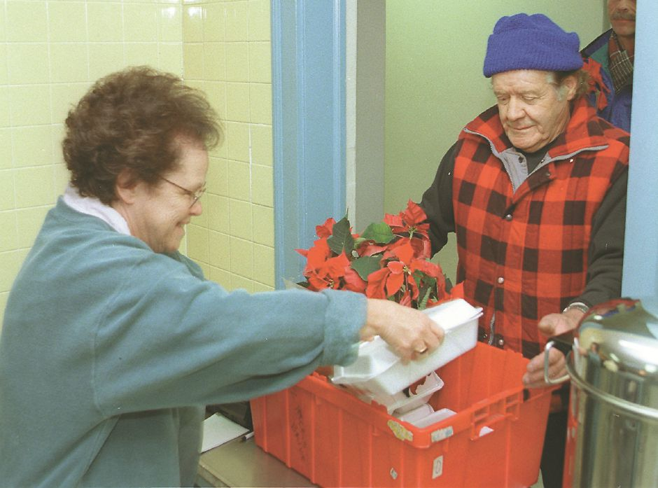 RJ file photo - Eve Gold places a hot turkey dinner into a box for fellow volunteer John Carini to deliver to an area family at the First Congregational Church in Wallingford Dec. 25, 1998.
