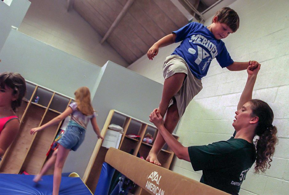 Chris Day, 8, gets a little help on the balance beam from instructor Kim Fox while participating with other kids in the YMCA