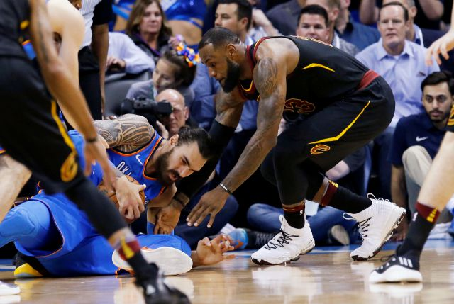 Cleveland Cavaliers forward LeBron James, right, reaches in for the ball held by Oklahoma City Thunder center Steven Adams during the first half of an NBA basketball game in Oklahoma City, Tuesday, Feb. 13, 2018. (AP Photo/Sue Ogrocki)