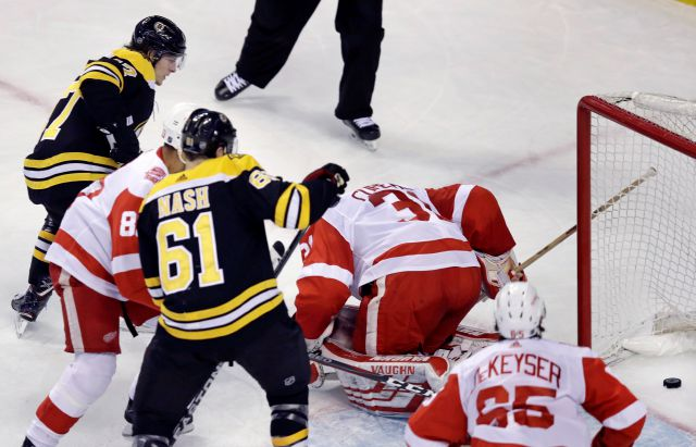 Boston Bruins defenseman Torey Krug, top left, watches his shot edge past Detroit Red Wings goaltender Jared Coreau (31) for a first-period goal, his second in the NHL hockey game in Boston, Tuesday, March 6, 2018. (AP Photo/Charles Krupa)