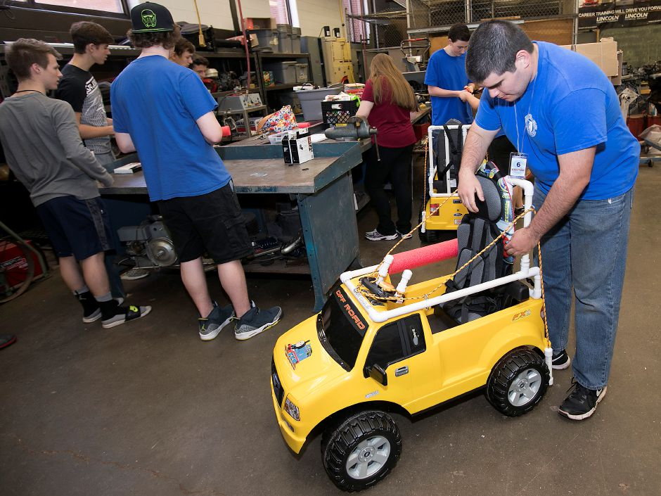 Central Connecticut State University student, Cody McQuarrie, 21, adjusts a seat while making final fittings to battery-powered cars for two special needs children at Southington High School Friday, May 11, 2018. Dave Zajac, Record-Journal