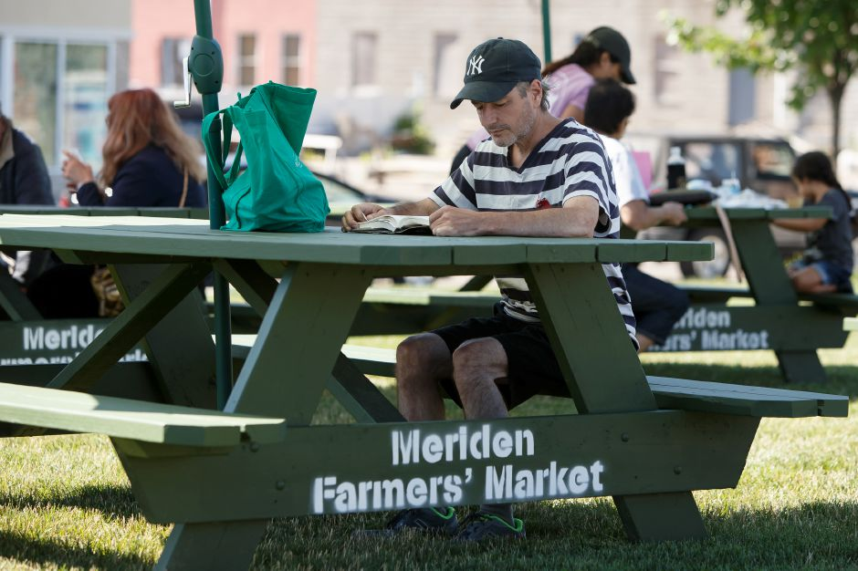 Thomas Trudeau of Meriden finds some shade at a picnic table to read Saturday during the Meriden Farmers Market at the Meriden Green in Meriden July 7, 2018 | Justin Weekes / Special to the Record-Journal