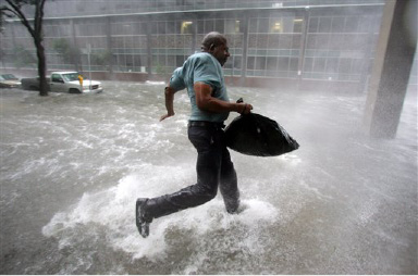 Arnold James tries to keep his feet as a strong gust nearly blows him over as he tries to make his way on foot to the Louisiana Superdome in New Orleans on Monday, Aug. 29, 2005.  The roof on James