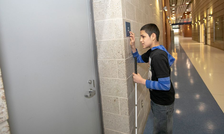 Sixth-grade student Jose Nieves Roman, 12, locates his occupational therapy room by reading a sign in braille at Lincoln Middle School in Meriden, Tues., Jan. 8, 2019. Dave Zajac, Record-Journal