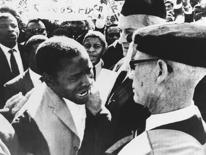 Professor J.P. Duminy, Vice Chancellor, foreground, of the Cape Town University (South Africa) is seen confronted by an angry demonstrating African students on Saturday, July 16, 1966 at the University College of Rhodesia, Salisbury, Zimbabwe. The flare-up started when white and black students clashed as a group of Africans tried to stop the graduation ceremony on the campus of the University, waving banners the students jostled whites around until they were finally broken up. During the ceremony they drowned white speakers be singing African nationalist songs. (AP Photo)