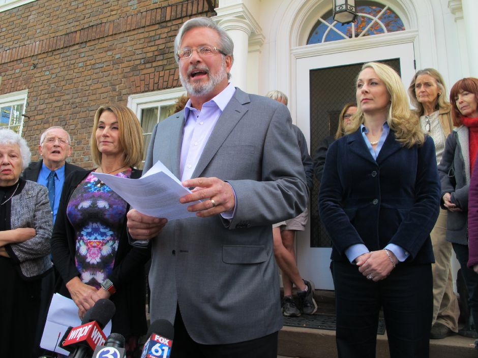 In this Oct. 26, 2016 file photo, Connecticut state legislative Republican candidate Dr. William Petit, flanked by state House Minority Leader Themis Klarides, R-Derby, left, and his wife, Christine, right, speaks to the media outside his home in Plainville, Conn. about a political advertisement linking him to Donald Trump and attacks on women and families. Petit
