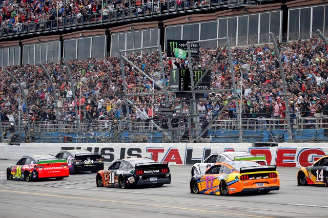 Pastor of First Baptist Church Dallas Dr. Robert Jeffress waves the green flag for the start of a NASCAR Cup Series auto race at Talladega Superspeedway in Talladega, Ala., Sunday, Oct. 13, 2019. (AP Photo/Butch Dill)