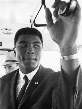 U.S. american boxer Muhammad Ali, former Cassius Clay, gets a grip on a handle in the airport shuttle bus taking him to the arrival hall after landing at Frankfurt am Main