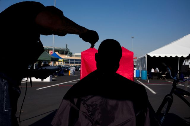 A homeless man, who declined to give his name, gets a free haircut in the parking lot of Angel Stadium during the community outreach day Tuesday, Dec. 19, 2017, in Anaheim, Calif. The event was organized by non-profit organizations and agencies to offer services to homeless people in Orange County. (AP Photo/Jae C. Hong)