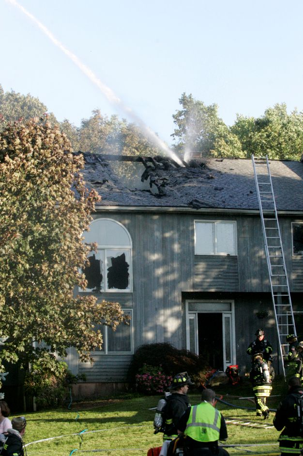 Cheshire firefighters shoot water through the roof of a home on Scenic Court that caught on fire, June 3, 2011. The cause of the fire is unknown but officials state two propane tanks were venting flames when firefighters arrived. Nobody was harmed and the family along with a cat and pet fish were able to get out safely. (Sarah Nathan/Record-Journal)