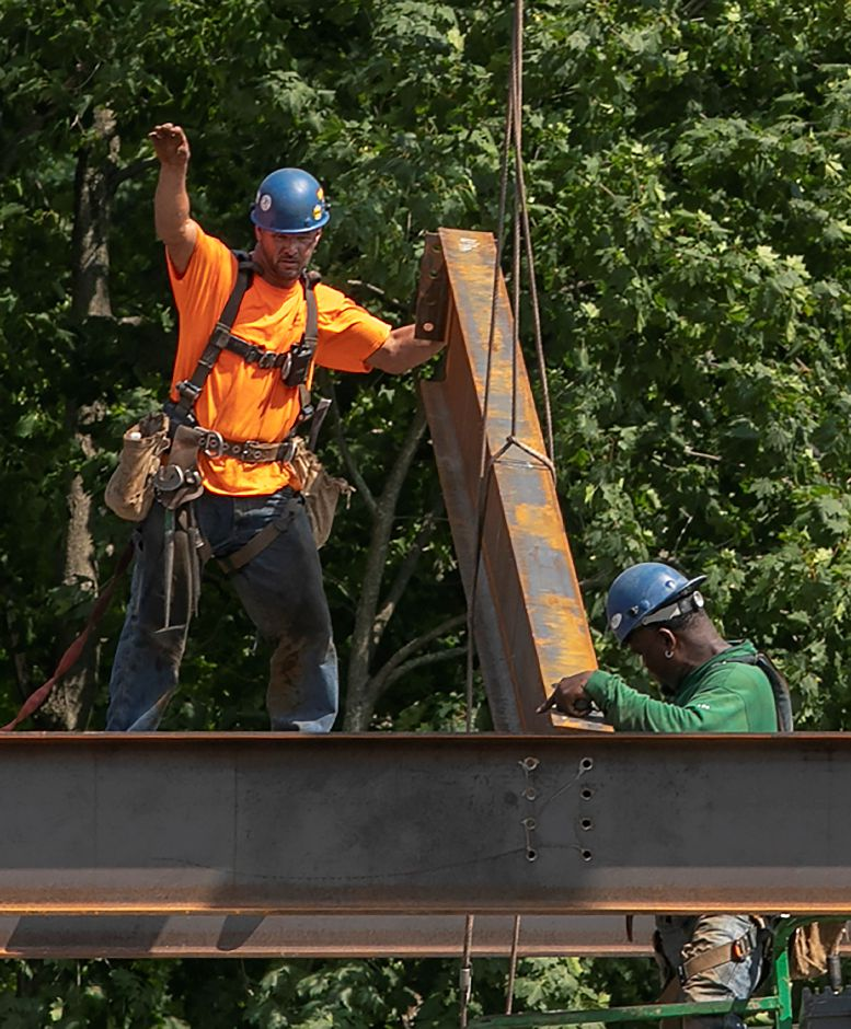 Workers help guide a beam into place as construction continues on the Hartford HealthCare medical facility under construction on South Main Street in Cheshire, Wednesday, August 15, 2018. Dave Zajac, Record-Journal