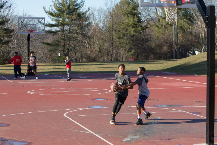 Chris Echevarria, 15, at left, and Kwali Rhodes, 14, both of Meriden, get a game of one-on-one in with temperatures reaching nearly 60 degrees Tuesda, Dec. 27, 2016 at Ceppa Field