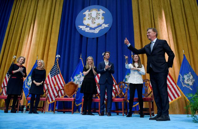 Connecticut Gov. Ned Lamont, right, gives a thumbs up after being sworn into office as his family looks on, Wednesday, Jan. 9, 2019, inside the William A. O
