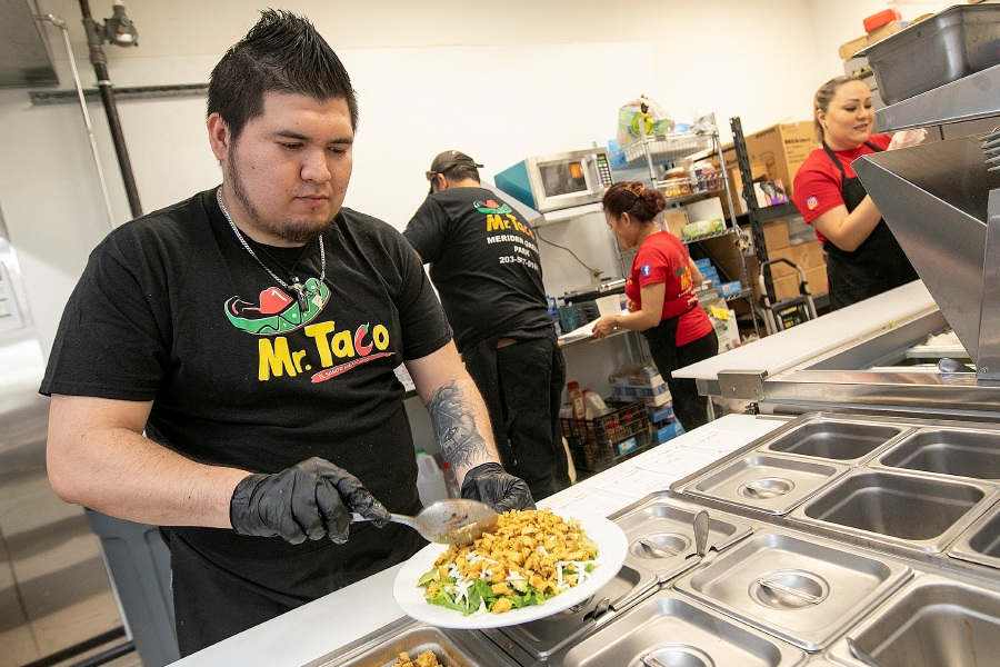 Cook Manolo Aguilar prepares a chicken salad at Mr. Taco, a new business at 69 Miller St. in Meriden on Tuesday.