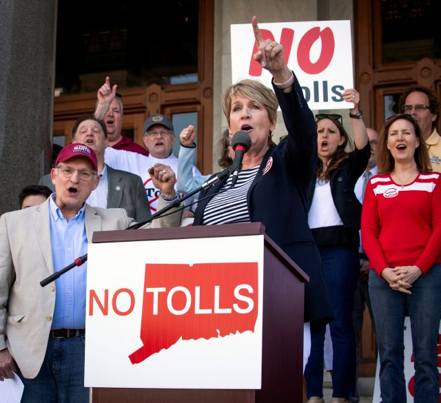 State Rep. Laura Devlin addresses the crowd of anti-toll protesters in front of the Capitol Building, Saturday, May 18, 2019 in Hartford, Conn. Protesters have gathered outside the state Capitol to rally against a proposal to put electronic tolls on the state
