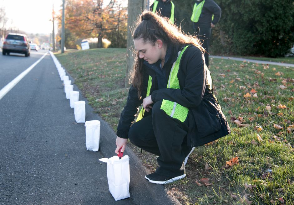 Dagny McKanley, 16, a junior at Cheshire High School, lights a luminary along Route 10 in Cheshire as part of the Mile of Hope on Saturday. Run by Cheshire charity Lights of Hope, the event raised money for local charities by selling the luminaries. | Devin Leith-Yessian/Special to the Record -Journal