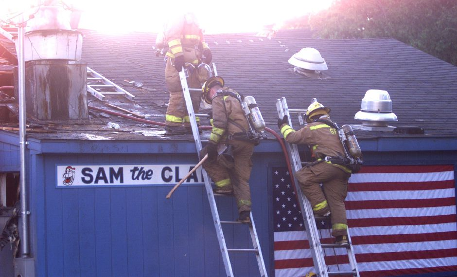 Southington fire fighters are getting off the roof of the Sam the Clam restaurant after venting the roof and extinguishing a kitchen fire that forced all the occupants out Saturday night, July 3.