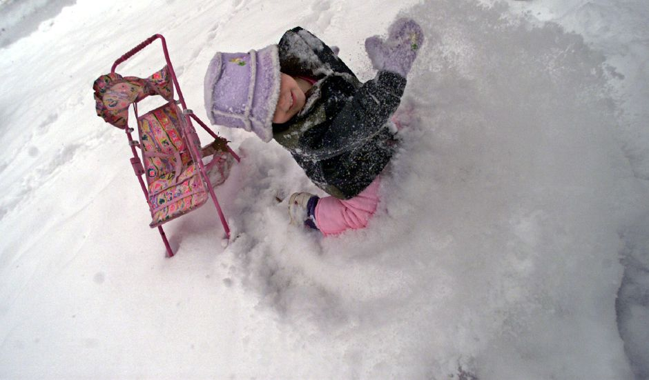 Aazzyria Perry ,3, of Meriden scoops away a storm of snow while making a path to push her toy stroller in the front yard of her residence on Brittania Street in Meriden Thursday afternoon December 5,2002 .