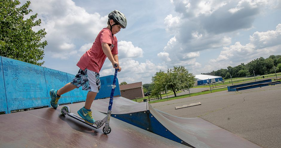 Brendin Dorin Pierce, 8, of Danbury, scoots down a ramp at the skate park at Bartlem Park in Cheshire, Friday, August 10, 2018. Richard Bartlem, the town's first parks department director and the namesake for Bartlem Park, is being remembered an active member of the local community. Bartlem died on Aug. 2 at 90 years old. Dave Zajac, Record-Journal