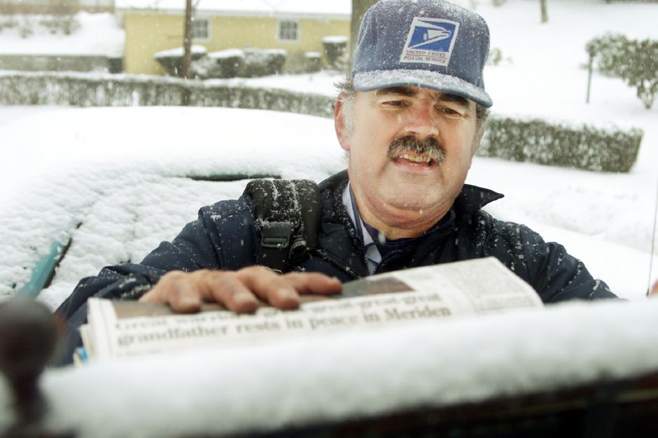 "Roland Marks weathers the snow as he stuffs a mailbox on his South Colony Street route in Meriden. Marks is a native of Southington and now lives in Meriden. ""It ain"