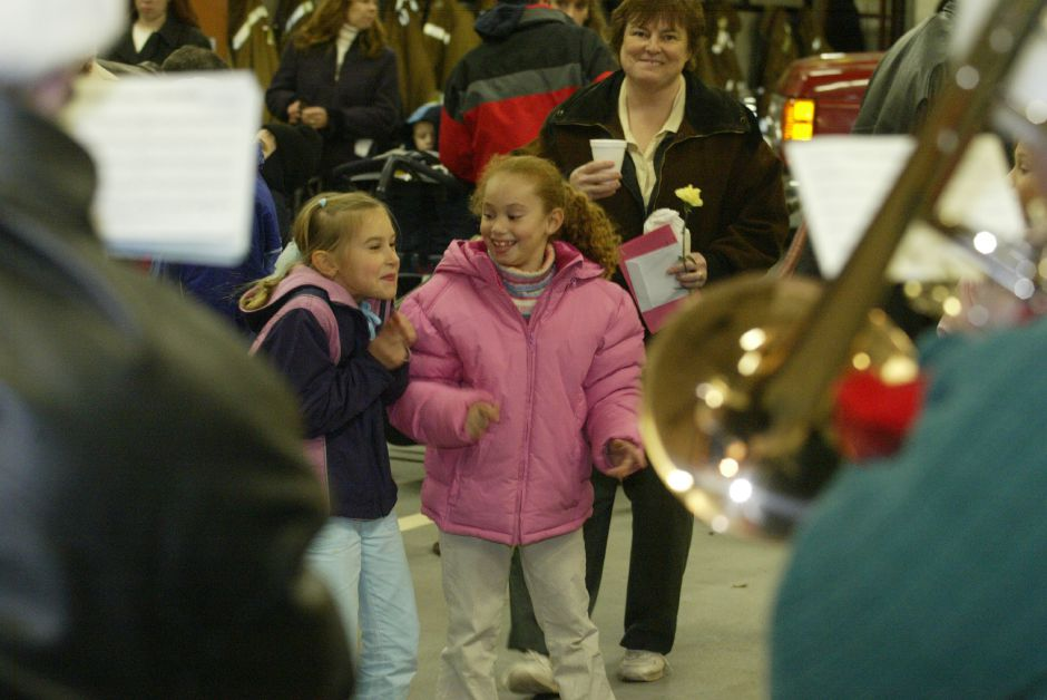 Erin Sullivan, 7, left, and Karla Ortiz, 6, right, both of Southington enjoy themselves to the Christmas Carols played by a brass quintet at the Southington Fire Department Company 2 station in Plantsville for the 15th Annual Christmas in the Village on Dec. 1, 2005.