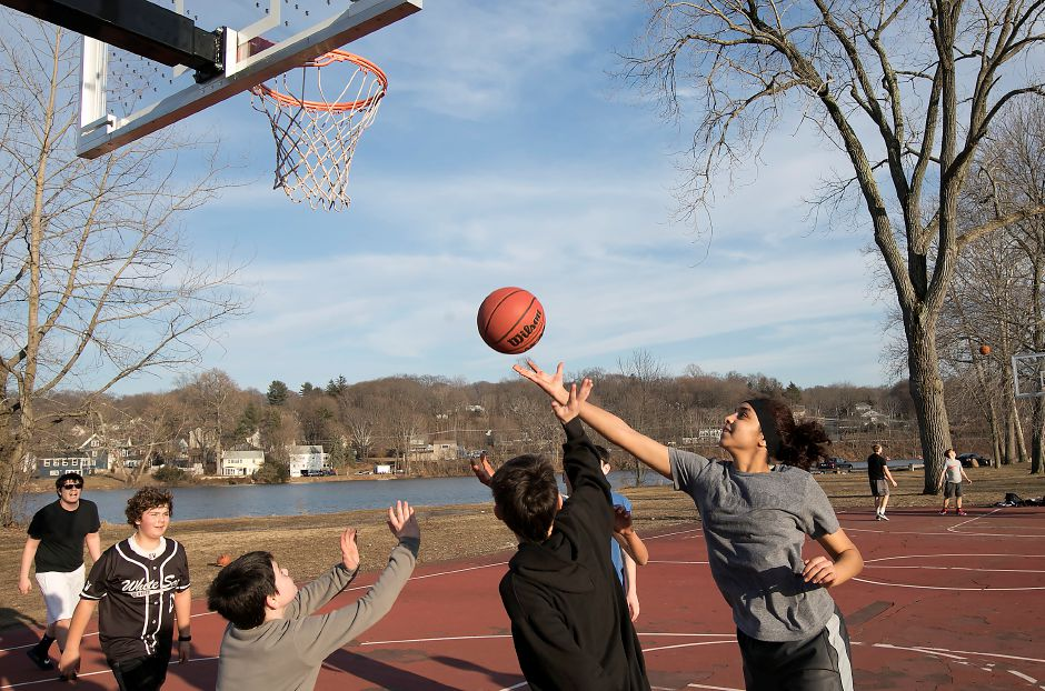 Toa Hassan, 15, of Meriden, takes a shot while playing basketball on a warm day at Habershon Park in South Meriden, Tuesday, Feb. 20, 2018. Dave Zajac, Record-Journal