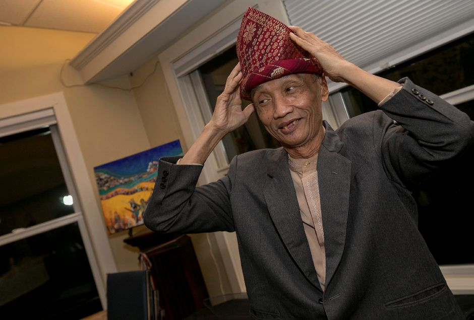 Sujitno Sajuti puts on a festive Indonesian hat during a celebration of his 69th birthday at the Unitarian Universalist Church on Paddock Avenue in Meriden, Wednesday, Dec. 13, 2017. Sajuti, an undocumented West Hartford resident, has taken up sanctuary at the Unitarian Universalist Church. Dave Zajac, Record-Journal